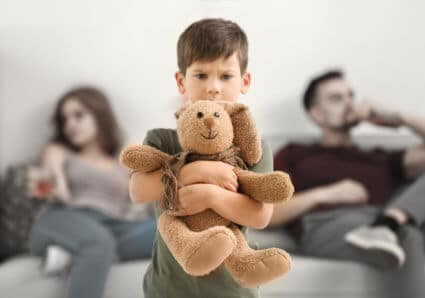 Little Boy Holding a Stuffed Bunny While His Parents Drink Representing National Children of Alcoholics Awareness Week